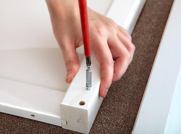 Montagem de móveis em casa, aparafusamento de buchas, chave de fenda.