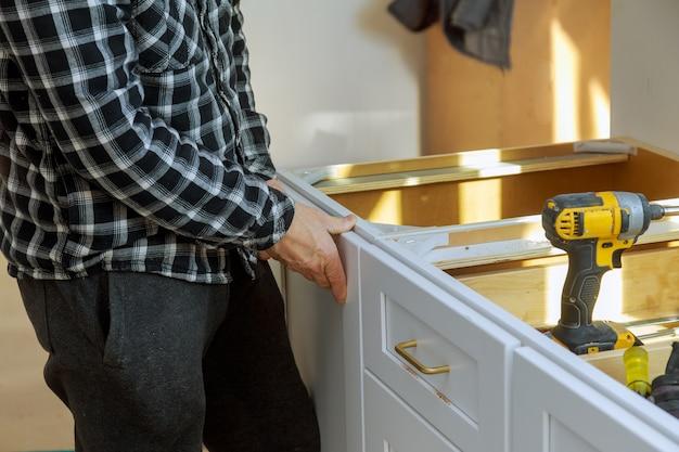 Montagem de parafusos de lata de lixo grande branco móveis usando uma chave de fenda.