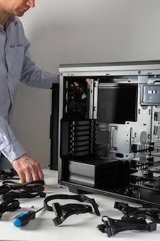 Montagem de um novo computador, mestre macho monta uma nova unidade de sistema, caixa aberta e cabos