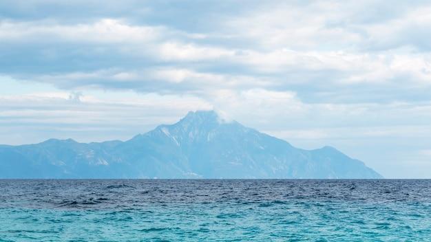 Montanha atingindo nuvens à distância com o mar egeu em primeiro plano na grécia