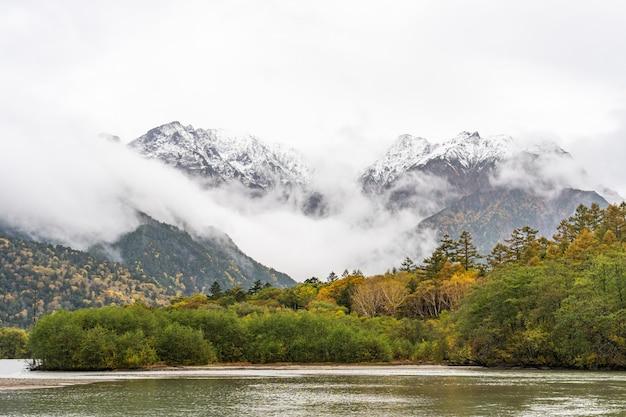 Montanha bonita na folha do outono com rio, kamikochi, parque nacional nos cumes do norte de japão da prefeitura de nagano, japão.