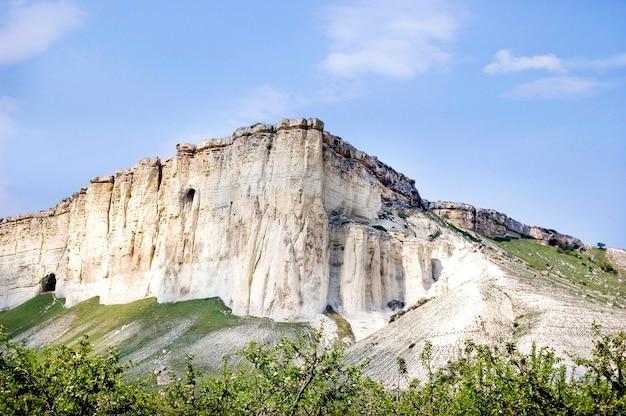 Montanha branca de pedra calcária na crimeia com cavernas, céu azul e verde perto das montanhas