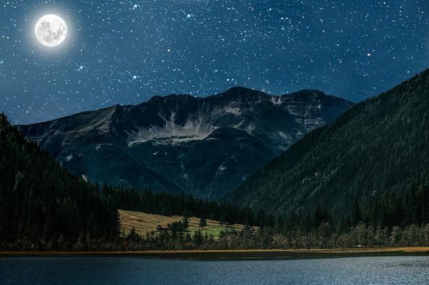 Montanha, céu noturno com estrelas e lua e nuvens.