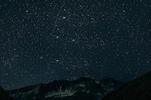 Montanha. céu noturno com estrelas, lua e nuvens.