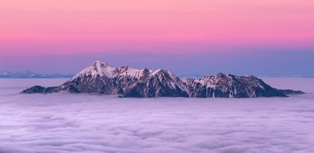 Montanha coberta de neve, cercada pelo mar de nuvens