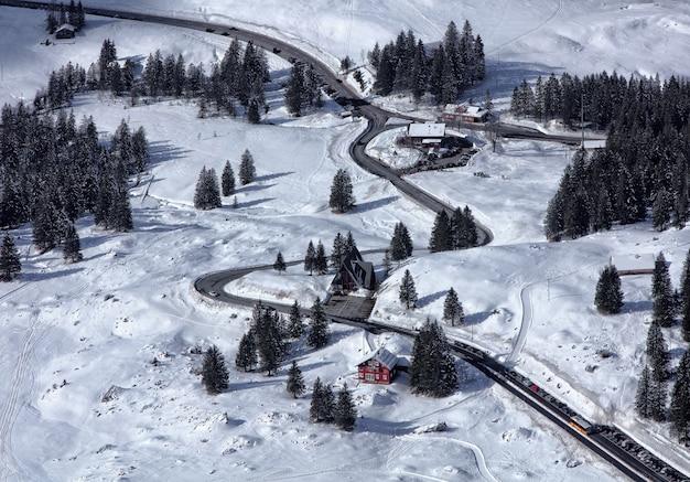 Montanha coberta de neve com estrada e árvores