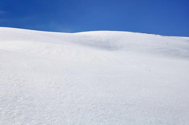 Montanha coberta de neve sob o céu azul