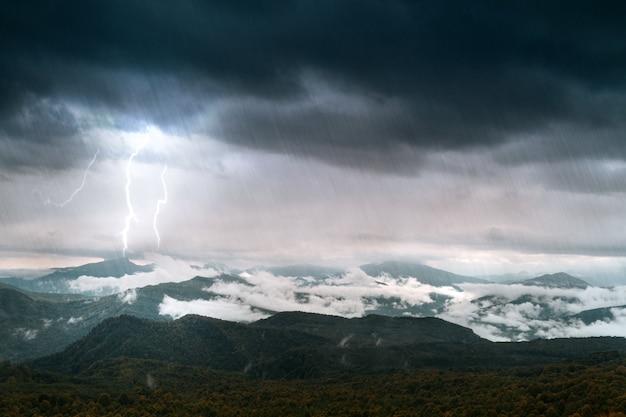 Montanha com céu e iluminação sob chuva