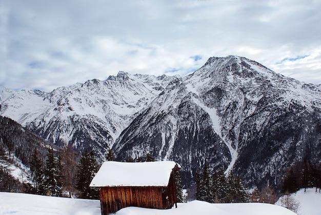Montanha com neve e casa de madeira