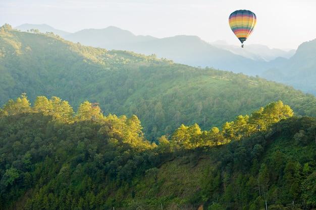 Montanha da floresta verde com balão de ar quente