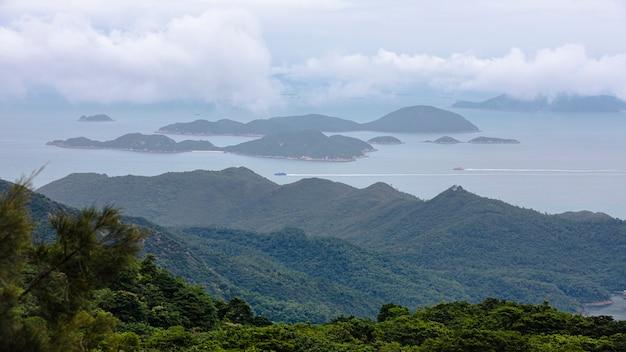 Montanha da paisagem e do seascape e os recipientes de carga do mar e de transporte na estação da chuva no ponto de vista ngong ping 360 teleférico em hong kong ásia