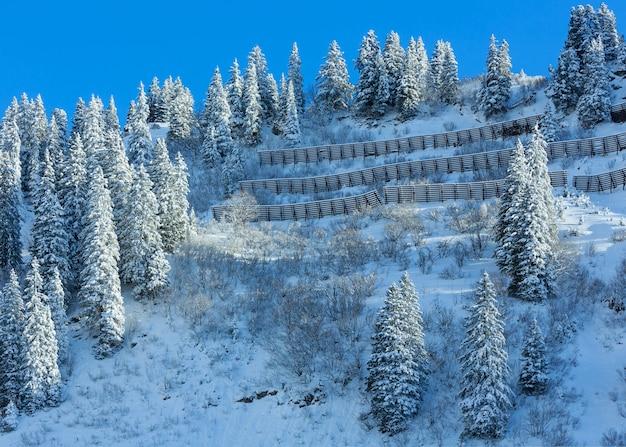 Montanha de inverno com abeto nevado e barreira de neve metálica na encosta.