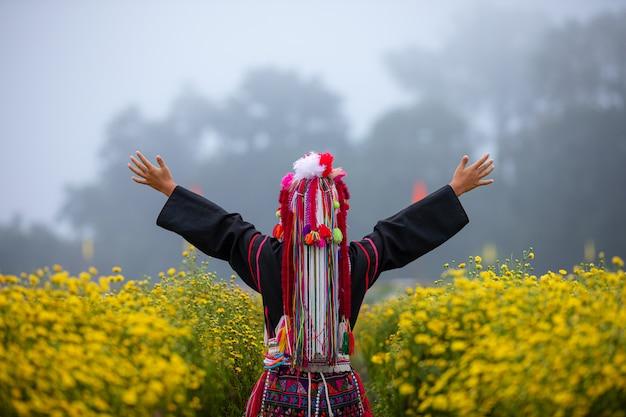 Montanha de karen tailandês levantar braços no campo de plantas de flores de crisântemos