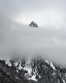Montanha de neve atrás de camadas de nuvens