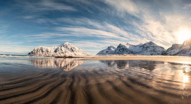 Montanha de neve com sulcos de areia na praia de skagsanden