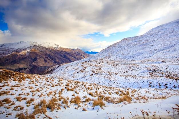 Montanha de neve e estrada da cordilheira da coroa entre a cidade de wanaka - queenstown, nova zelândia