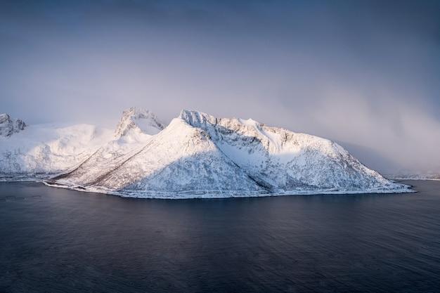 Montanha de neve na nevasca no círculo ártico ao nascer do sol. ilhas senja, noruega