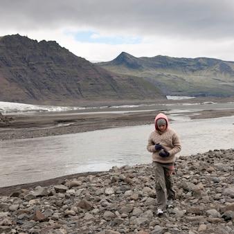Montanha erodindo ao lado da margem do rio glacial e morena rochosa com garota
