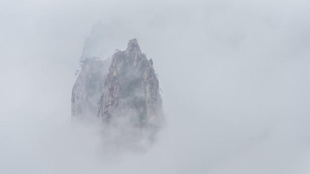 Montanha flutuando acima das nuvens do mar branco