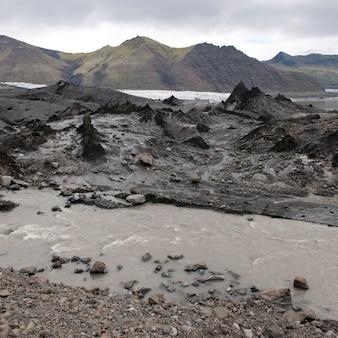 Montanha, geleira icefield e córrego enlameado