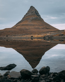 Montanha kirkjufell perto do parque nacional snaefellsjokull, islândia refletida no lago