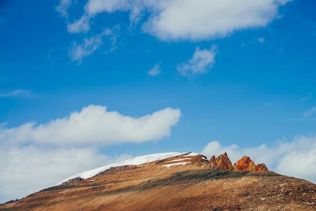 Montanha linda e ensolarada com penhascos marrom-laranja-avermelhados no topo sob o céu azul