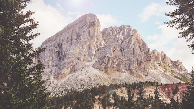 Montanha marrom perto de árvores verdes sob um céu nublado branco e azul ensolarado
