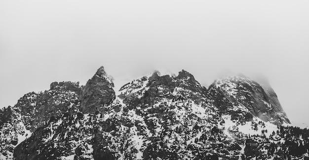 Montanha preta e branca com neve e nevoeiro
