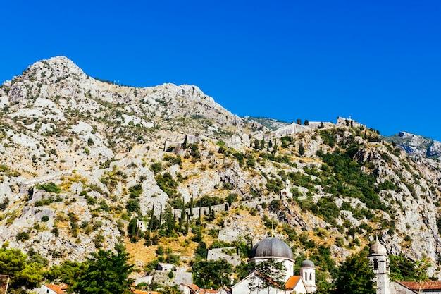 Montanha rochosa branca com árvores verdes contra um céu azul