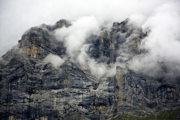 Montanha rochosa coberta por nuvens espessas