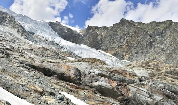 Montanha rochosa e snowfield de uma geleira nos alpes europeus