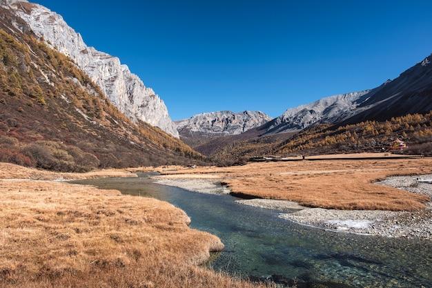 Montanha tibetana sagrada com prado dourado e rio no outono