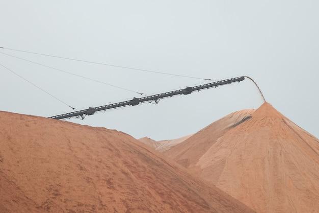 Montanhas amarelo-escuras de depósitos de sal em cima das quais há uma máquina de extração de sal