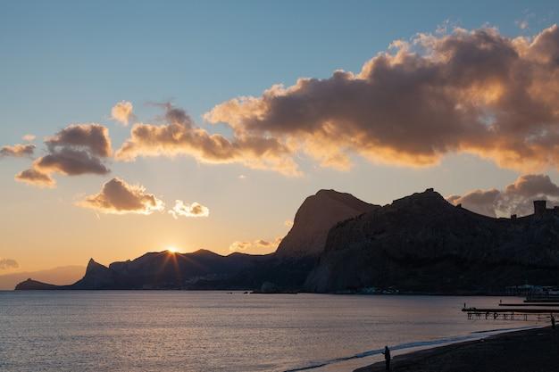 Montanhas ao pôr do sol à beira-mar