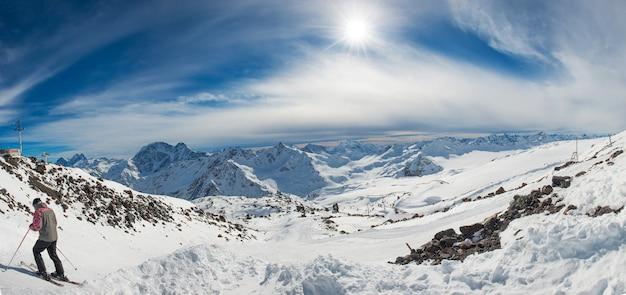Montanhas azuis na neve com nuvens. panorama com esquiador