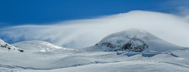 Montanhas brancas do inverno cobertas de neve no céu nublado azul. alpes. áustria. pitztaler gletscher