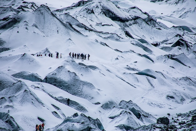 Montanhas brancas e nevadas com os viajantes de caminhadas