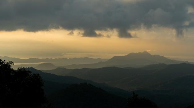 Montanhas cênicas do panorama, luz solar dourada da manhã enevoada.