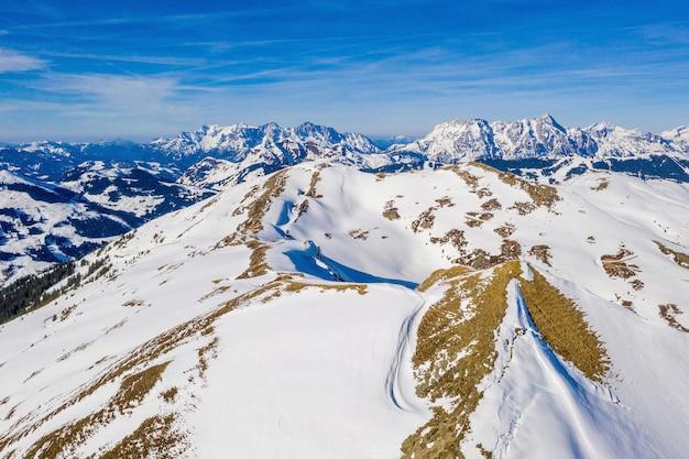 Montanhas cobertas de neve de saalbach-hinterglemm sob um céu azul claro