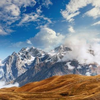 Montanhas cobertas de neve na névoa. outono no lago koruldi