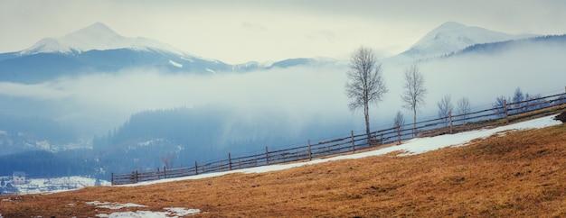 Montanhas cobertas de neve na névoa.