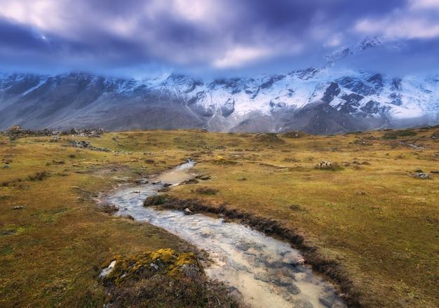 Montanhas com picos cobertos de neve, rio pequeno, grama amarela e céu nublado ao pôr do sol