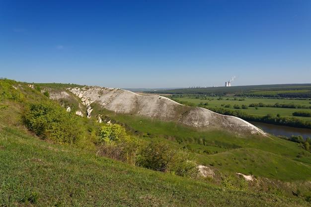 Montanhas de giz nas margens do rio don, na rússia central. vista da paisagem das colinas. central nuclear no horizonte.