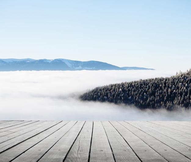 Montanhas de inverno com neblina e piso de madeira