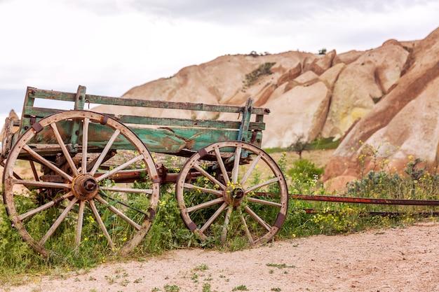 Montanhas de pedra calcária nos vales da capadócia. carrinho de madeira velho, closeup. grande paisagem.