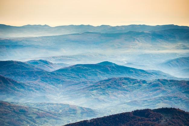 Montanhas e colinas azuis sob um lindo pôr do sol laranja