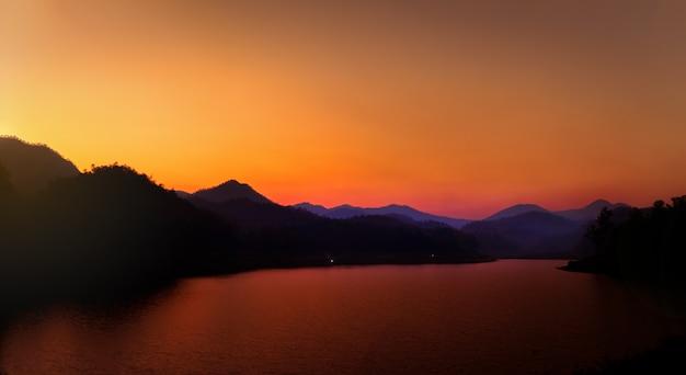 Montanhas e lago ao pôr do sol