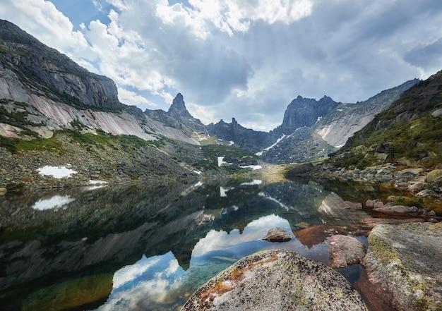 Montanhas e lagos fabulosos, viagens e caminhadas, vegetação exuberante e flores ao redor. água de nascente descongelada das montanhas