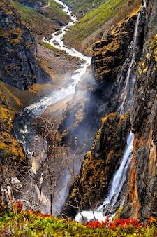 Montanhas e riacho de água fluindo de uma rocha no vale, noruega