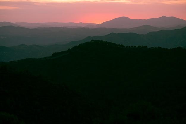Montanhas em preto com céu rosa